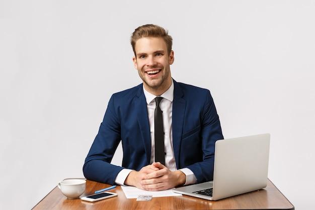 Piacevole uomo d'affari affascinante con i capelli biondi, abito da barba, seduta in ufficio con relazione, laptop, cliente amichevole di consulenza sorridente, conversazione d'affari con i dipendenti, sfondo bianco