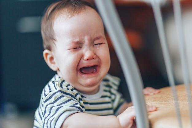 Piangendo una ragazzina dai capelli biondi, sta piangendo rumorosamente, in piedi vicino alla sedia di casa