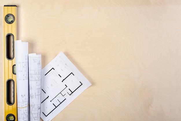 Piani architettonici distesi sulla scrivania con copia-spazio