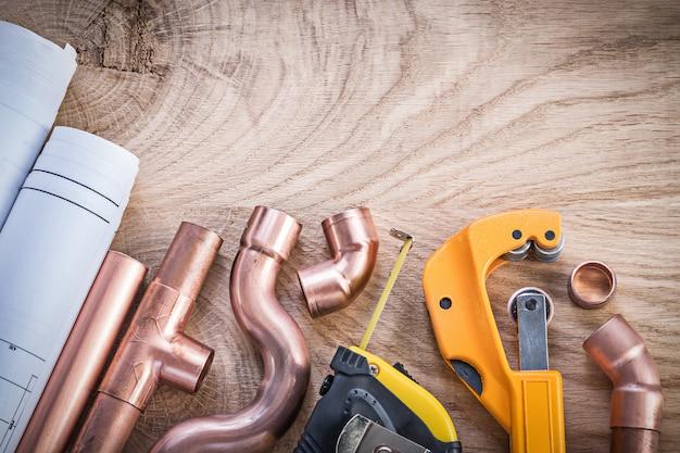 Piani di costruzione che misurano i connettori della taglierina della tubatura dell'acqua del nastro sul concetto dell'impianto idraulico del bordo di legno