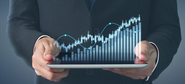 Pianificare la crescita del grafico e l'aumento degli indicatori positivi del grafico nella sua attività, tablet in mano