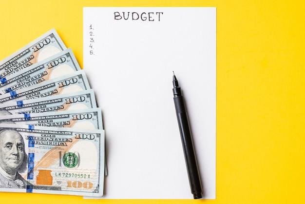 Pianificazione del concetto di budget. blocco note con il bilancio di parola e le banconote in dollari su giallo