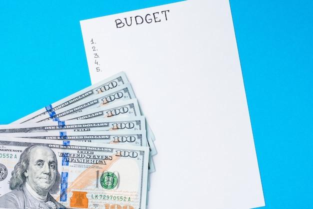 Pianificazione del concetto di budget. blocco note con il bilancio di parola e le banconote in dollari sul blu