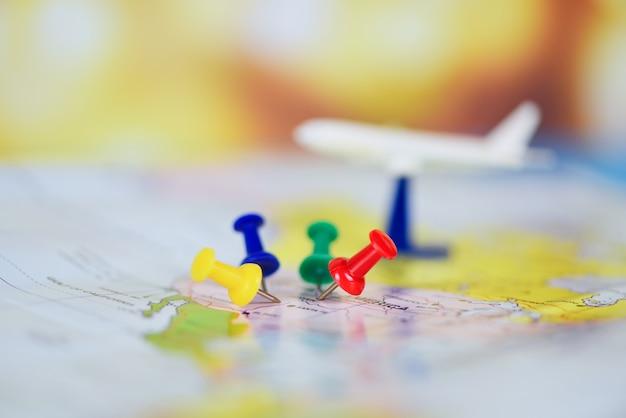 Pianificazione del viaggio con i punti di destinazione dell'aeroplano su un perno della mappa, tempo di viaggio o piano per il concetto di viaggio