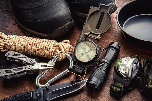 Pianificazione dell'attrezzatura di viaggio all'aperto per un viaggio di campeggio di trekking della montagna su fondo di legno