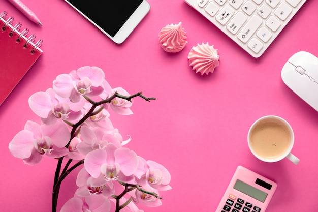 Pianificazione delle celebrazioni: carte per cellulare, tastiera, caffè e invito con orchidee su carta rosa