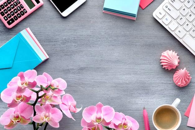 Pianificazione delle celebrazioni: carte per cellulare, tastiera, caffè e invito con orchidee su legno grigio