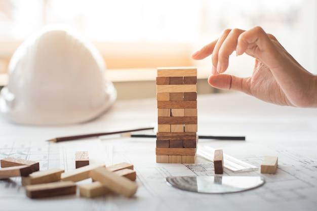 Pianificazione, rischio e strategia nei settori degli affari, degli imprenditori e degli ingegneri che fanno un blocco di legno su una torre.