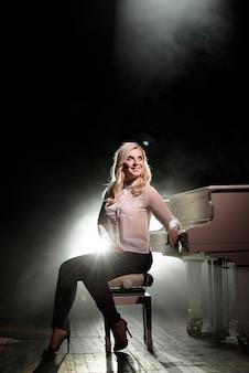 Pianista in posa vicino al piano bianco sul palco.