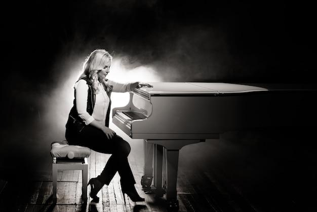 Pianista in posa vicino al piano bianco sul palco