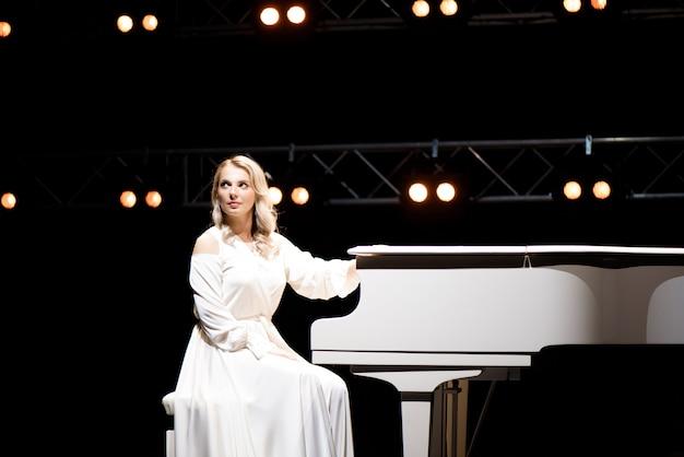 Pianista in posa vicino al pianoforte bianco sul palco