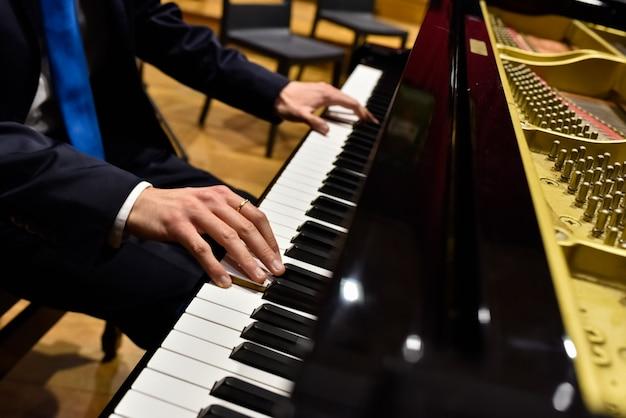 Pianista professionista che esegue un brano su un pianoforte a coda.