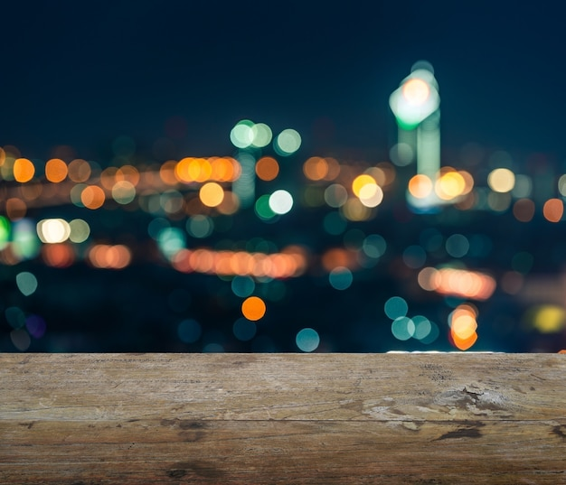 Piano d'appoggio di legno con fondo astratto vago della vista del centro città delle luci notturne di bangkok con bokeh
