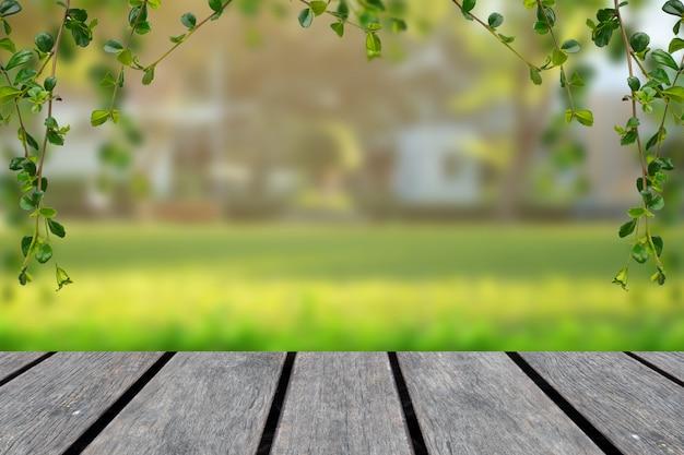 Piano d'appoggio di legno con fondo verde della sfuocatura con gli alberi nel parco con la struttura della vite