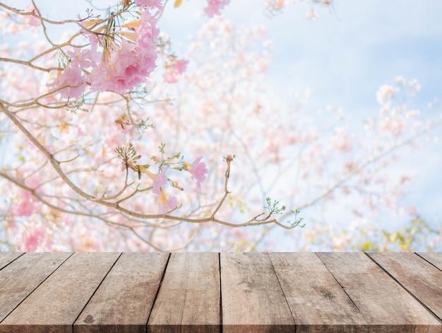 Piano d'appoggio di legno e fondo vago dei fiori con il filtro d'annata