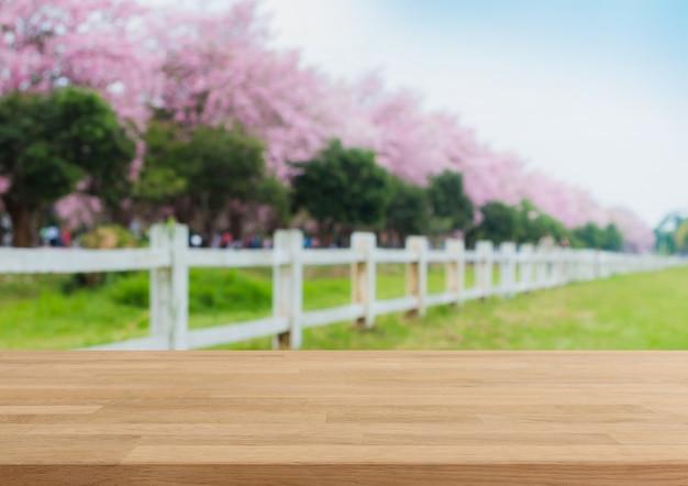 Piano d'appoggio di legno ed albero vago del fiore nel fondo del giardino con il filtro d'annata