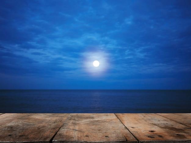 Piano d'appoggio di legno sopra la spiaggia di estate alla notte con la luna piena