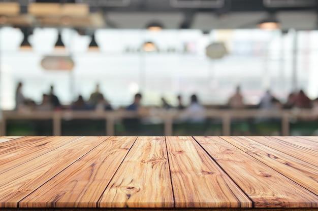 Piano d'appoggio di legno su fondo vago della caffetteria interna o del fondo della caffetteria del caffè della sfuocatura del ristorante