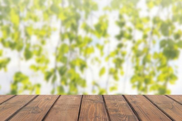 Piano d'appoggio di legno sul fondo astratto della sfuocatura con i rami della betulla