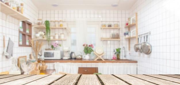 Piano d'appoggio di legno sul fondo della stanza della cucina della sfuocatura. per l'esposizione del prodotto del montaggio o la disposizione visiva chiave di progettazione