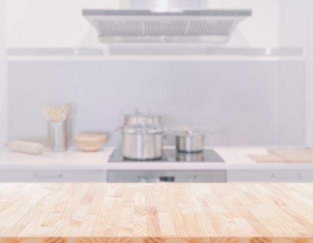 Piano d'appoggio di legno sul fondo della stanza della cucina della sfuocatura. può essere utilizzato per visualizzare o montare i tuoi prodotti.