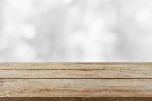 Piano d'appoggio di legno vuoto con fondo bianco vago. può essere utilizzato per visualizzare o montare i tuoi prodotti.