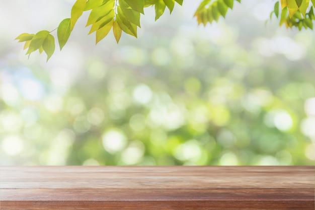 Piano d'appoggio di legno vuoto e vista vaga dal fondo verde del bokeh del giardino dell'albero