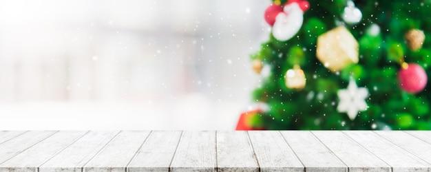 Piano d'appoggio di legno vuoto sulla sfuocatura con l'albero di natale del bokeh e la decorazione del nuovo anno sul fondo della finestra