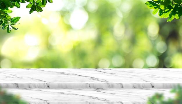 Piano d'appoggio di marmo bianco vuoto con l'albero della sfuocatura in parco con la luce del bokeh a fondo