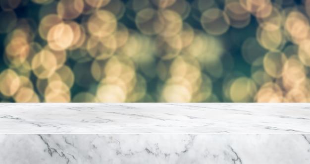 Piano d'appoggio di marmo con l'albero di natale astratto della sfuocatura con la luce della corda della decorazione con la luce del bokeh, contesto di vacanza invernale