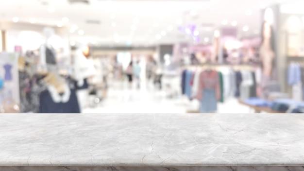 Piano d'appoggio di marmo di pietra bianco vuoto ed interno astratto vago dal fondo del centro commerciale.
