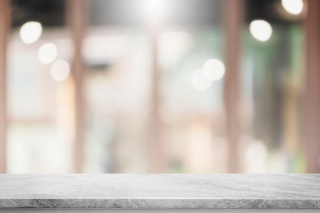 Piano d'appoggio di pietra di marmo bianco vuoto e fondo interno dell'insegna del ristorante della finestra di vetro della sfuocatura.