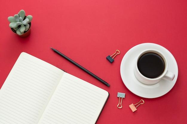 Piano d'appoggio, scrivania funzionante con il taccuino aperto e tazza di caffè su fondo rosso. copia spazio per il testo.