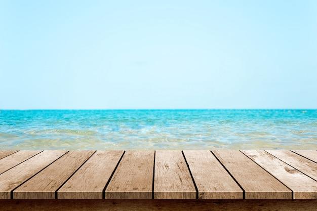 Piano del tavolo in legno con spiaggia di sfocatura