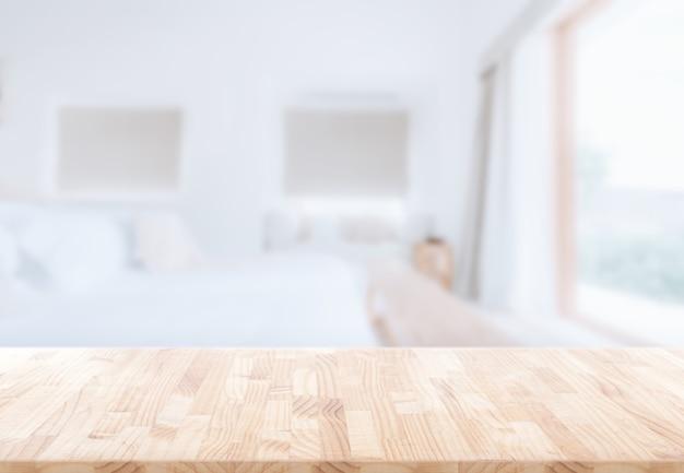 Piano del tavolo in legno davanti all'interiore della camera da letto offuscata