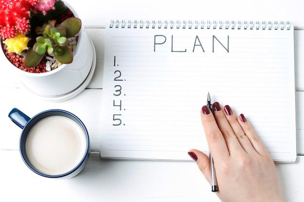 Piano di iscrizione in blocco note, primo piano, vista dall'alto, concetto di pianificazione, impostazione degli obiettivi