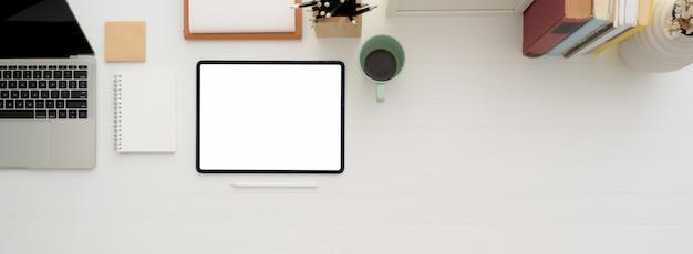Piano di lavoro minimale con tablet mock-up, tazza di caffè, quaderni, articoli di cancelleria e copia spazio sulla scrivania bianca