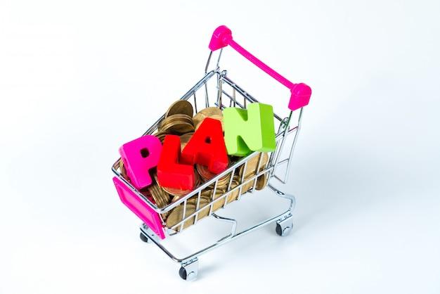 Piano di testo e pile di monete con carrello della spesa o carrello del supermercato, isolato