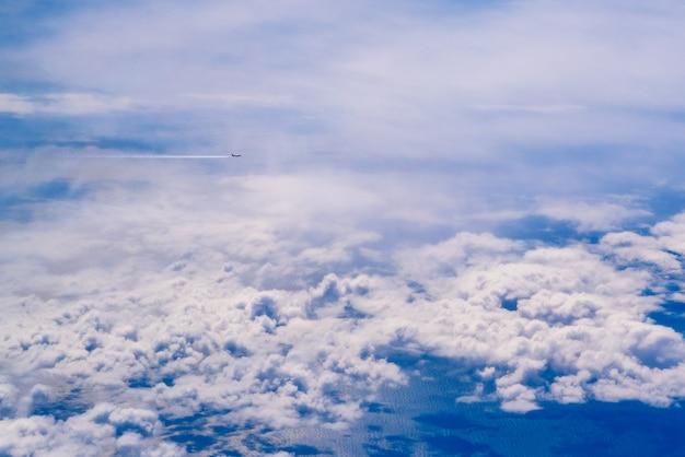 Piano di voli commerciali che attraversano un cielo di nuvole bianche e blu visto dall'alto, sul mediterraneo.