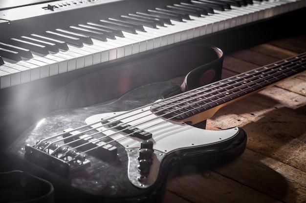 Piano e chitarra sul primo piano di legno del fondo