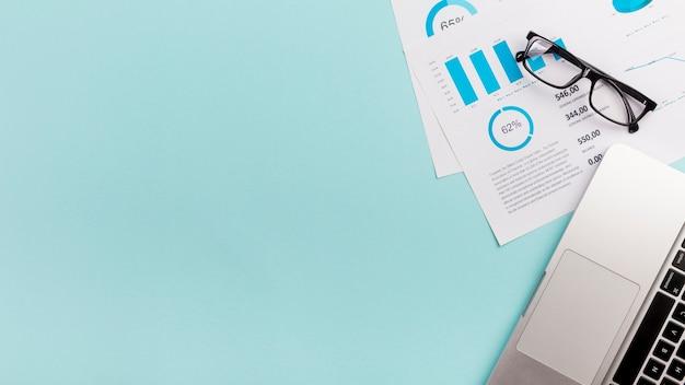 Piano, occhiali e computer portatile del bilancio aziendale su fondo blu