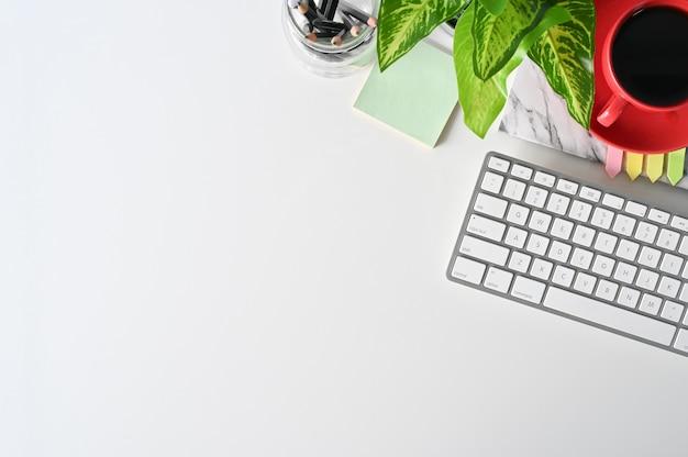 Piano tavolo da ufficio con computer, cuffia, matita, caffè e decorazione vegetale.