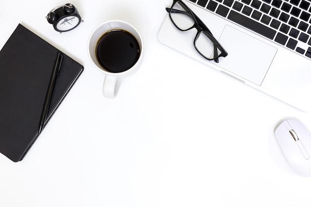 Piano tavolo da ufficio laici del posto di lavoro moderno con il computer portatile sul tavolo bianco