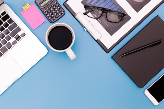 Piano tavolo da ufficio laici del posto di lavoro moderno con il computer portatile sul tavolo blu