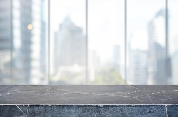 Piano tavolo in pietra e sfocatura dello sfondo della parete vetrata - può essere utilizzato per la visualizzazione o il montaggio dei tuoi prodotti.