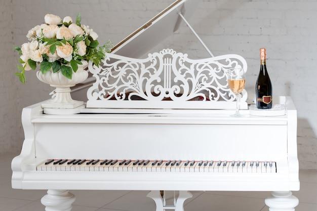 Pianoforte a coda in un lussuoso interno bianco classico con vino, palme e fiori.