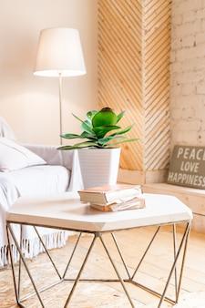 Pianta domestica posizionata su un tavolino nell'interno luminoso della stanza con dipinti, piante in vaso e lampada da terra. interni eleganti del soggiorno con tavolino e divano di design.