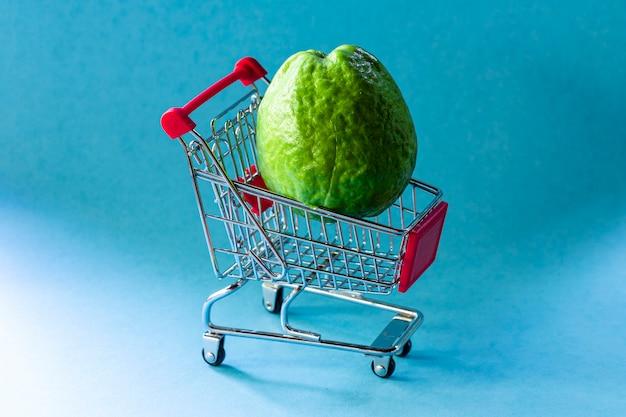 Piante di guaiava rossa dentro il carretto del supermercato su fondo blu