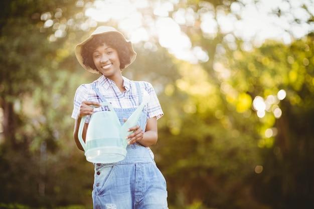Piante di innaffiatura sorridenti della donna nel giardino