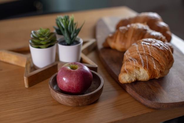Piante grasse, cornetti, mela rossa su un tavolo di legno